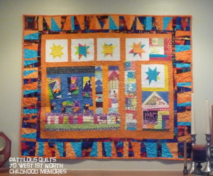 """P Ferguson artist. """"I made this quilt last summer as part of a challenge.  The border needed to be something special and then I found that wonderful Robert Kaufman fabric that I'd purchased from you, but hated to cut into it because it was so pretty.  When I thought about how fun the border would be that fear of the first cut went away.  The quilt is called 70 W 1st North.  It has semblance of the house I lived in as a child and the house with the heart in the window is where I was welcomed to visit. """""""
